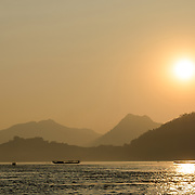 The sun just before it sets behind the hills next to the Mekong River near Luang Prabang in central Laos.