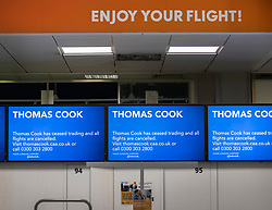 © Licensed to London News Pictures. 23/09/2019. Gatwick, UK. A sign says 'ENJOY YOUR HOLIDAY' above closed Thomas Cook check-in desks at Gatwick Airport after the travel firm collapsed. The 178 year old travel operator has gone in to liquidation after rescue talks failed overnight. This will trigger the largest peacetime repatriation as more than 150,000 British holidaymakers will need to be brought home. Photo credit: Peter Macdiarmid/LNP