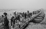 Hindu pilgrims cross one of the pontoon bridges on their way to the Kumbh Mela festival.  Prayagraj, India.