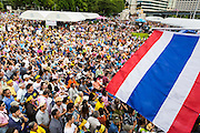 04 AUGUST 2013 - BANGKOK, THAILAND: The Thai flag frames the the crowd of about 2,000 people, members of the  People's Army against Thaksin Regime, a new anti-government group, protested in Lumpini Park in central Bangkok. The protest was peaceful but more militant protests are expected later in the week when the Parliament is expected to debate an amnesty bill which could allow Thaksin Shinawatra, the exiled former Prime Minister, to return to Thailand.     PHOTO BY JACK KURTZ