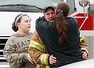 Oso fire department firefighter Mark Upthegrove weeps and gets a hug from a family member after a moment of silence for those lost in the mudsilde exactly one week ago in Oso, Washington March 29, 2014.  Family and friends of 90 people still missing after a wall of mud flattened the outskirts of a rural Washington state town increasingly feared for the worst on Saturday as the governor called for a statewide moment of silence a week after the disaster. REUTERS/Rick Wilking(UNITED STATES)