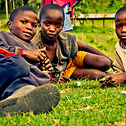 Children relax on the green grass of Taachasis. Nandi County, Kenya's Rift Valley Province.