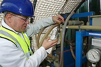 scientist checking purity of water being cleaned by electical filter system