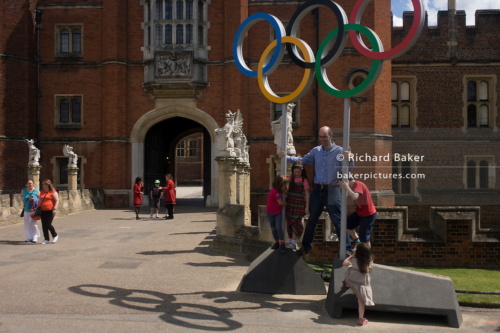 Family stands for a souvenir photo on the Olympic rings that stand at the entrance of King Henry the Eighth's Hampton Court Palace on the first day of competition of the London 2012 Olympic 250km mens' road race. Starting from central London and passing the capital's famous landmarks before heading out into rural England to the gruelling Box Hill in the county of Surrey. Local southwest Londoners lined the route hoping for British favourite Mark Cavendish to win Team GB first medal but were eventually disappointed when Kazakhstan's Alexandre Vinokourov eventually won gold.