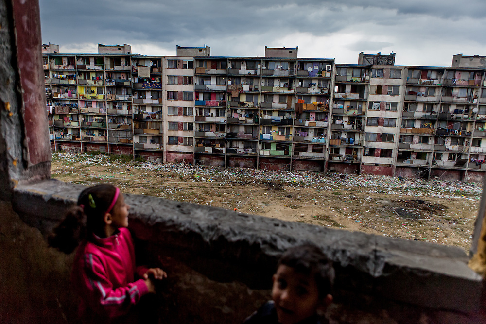 """Children looking out of the decrepit highrise building """"Hrebenova 34-36"""" which was demolished by the city of Kosice in August 2014. The Lunik IX housing estate is home to the largest Roma community in Slovakia. It is located a few kilometers away from the historical city centre, on the outskirts of the eastern Slovakian city of Kosice. Since the beginning of the 1980s a large number of the Roma residents living in the city and in nearby settlements have been moved to Lunik IX. Lunik IX has officially 6542 registered (12/2015) inhabitants and almost all of them are of Roma ethnicity."""