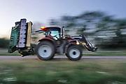 Nederland, Ubbergen, 30-6-2020  Een boer, loonwerker, rijdt met de tractor over de provinciale weg naar huis, het bedrijf . Het is al avond en hij heeft zijn zwaailicht aan om goed zichtbaar te zijn . Foto: ANP/ Hollandse Hoogte/ Flip Franssen