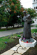 Statue of Saint Francis (Sveti Franjo), with live pigeons feeding at his feet. Sibenik, Croatia