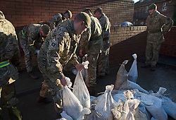 © Licensed to London News Pictures. 29/12/2015. York, UK.  Soldiers from 2nd Battalion The Yorkshire Regiment help sandbag a British Telecom building to protect it from further flooding in the centre of York on December 29, 2015. Further rainfall is expected over coming days as Storm Frank approaches the east coast of the country. Photo credit: Ben Cawthra/LNP