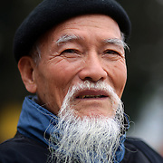 A portrait of an elderly Vietnamese gentleman, sitting beside Hoan Kiem Lake, Hanoi, Vietnam. Hanoi is the capital of Vietnam and the country's second largest city. Hanoi, Vietnam. 17th March 2012. Photo Tim Clayton