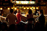 Young people at the bar in a cool edgy bar in Havana old town, drinking and chatting in the low, atmospheric lighting, Havana, Cuba.