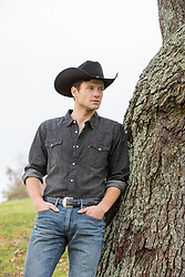 cowboy leaning on a tree