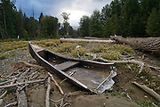 A broken canoe lies amid woody debris on a sand bank in the Cle Elum River near Cle Elum, Washington.
