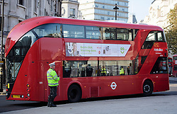 © Licensed to London News Pictures. 11/11/2016. London, UK. A bus stood still and a police officer mark a minutes silence during Silence in the Square, a service held in Trafalgar Square, London to mark Remembrance Day. A minutes silence is held on the 11th hour of the 11th day of the 11th month, to recall the end of hostilities of World War I.  Photo credit: Ben Cawthra/LNP