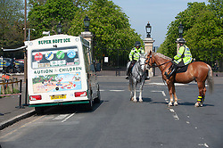 ©Licensed to London News Pictures 15/04/2020  <br /> Greenwich, UK. Mounted police officers running a check for permission to work on the ice cream man outside Greenwich park. Police on patrol in Greenwich park, Greenwich, London as people get out of the house from coronavirus lockdown to exercise for an hour. Photo credit:Grant Falvey/LNP