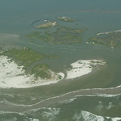 Oil containment boom is laid out in an effort to protect marshlands off the coast of Louisiana in the Gulf of Mexico, U.S., on Saturday, May 1, 2010. The BP Plc Deepwater Horizon drilling rig oil spill is threatening the wildlife that inhabit the barrier islands off the Louisiana coast. Photographer: Derick E. Hingle.