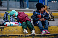 ATHENS, GREECE - FEBRUARY 04: Two young refugees sit on the ground outside the Pireaus port after disembarking a ferry from the Greek islands on February 04, 2015 in Athens, Greece. Thousands of refugees arrive every day by ferries fleet by private companies from the Greek islands to the Pireaus port, those with money can afford to buy tickets for the buses that will take them to the Macedonian border, but those arriving without money had to wait outside the Pireaus port for assistance or occupy spaces on public square in Athens where they will spend their days until the can travel Idomeni, near de Macedonian border. Photo: © Omar Havana. All Rights Are Reserved
