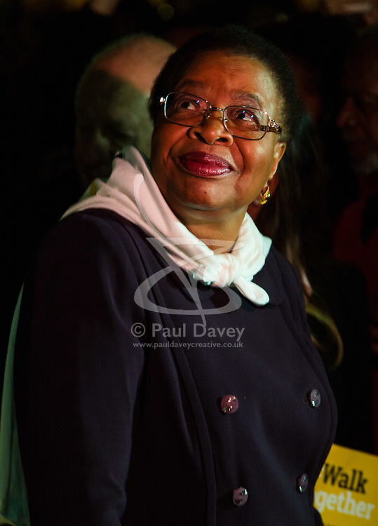 """London, October 23 2017. Nelson Mandela's group of Elders including former UN Secretary General Kofi Annan and Secretary General Ban Ki-moon accompanied by his widow Graca Machel gather at Parliament Square at the start of the Walk Together event in memory of Nelson Mandela before a candlelight vigil at his statue in Parliament Square. """"WalkTogether is a global campaign to inspire hope and compassion, celebrating communities working for the freedoms that unite us"""". PICTURED: Graca Machel looks up at the statue of her late husband in Parliament Square. © Paul Davey"""