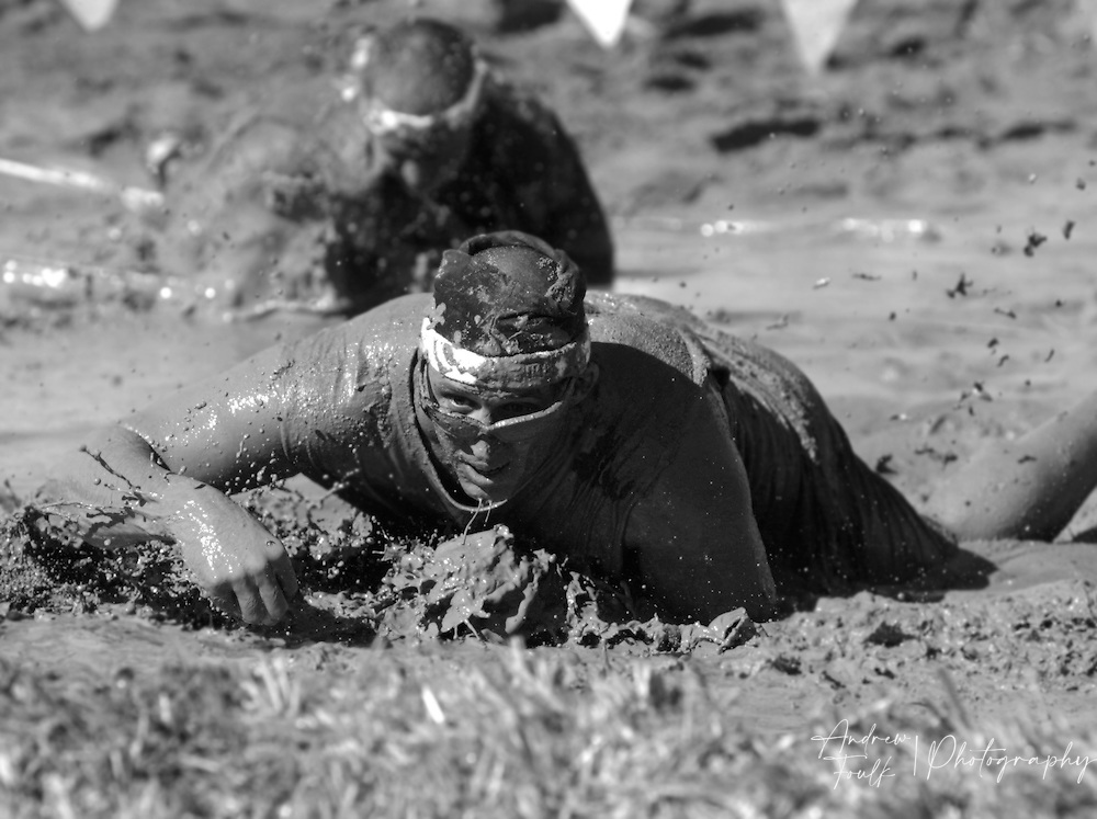 /Andrew Foulk/ For The Californian/ .Competitors in the Lake Elsinore Gladiator Run, crawl their way through one of the two mud pits during the 5K run.