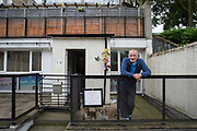 Ronald Cray, with dogs Mitch and Killy, at his home in Central Hill Estate on 18th June 2016 in South London, United Kingdom. Mr Cray has been a council tenant for 50 years and lived at Central Hill Estate for about two years. Central Hill is a low-rise estate of more than 450 homes in Crystal Palace in South London and has been recommended for demolition under Lambeth Council estate regeneration plan. The housing scheme, built between 1966 and1974, was designed by Rosemary Stjernstedt under Lambeth Council's director of architecture, Ted Hollamby.