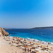 People swim and sunbathe on Kaputas beach, turquoise beach, Turkey
