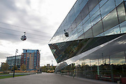 An Emirates Air Line Cable Car passes by The Crystal building in Royal Victoria Docks London, England, United Kingdom.  The Air Line opened in 2012  and was built by Doppelmayr with sponsorship from the airline Emirates.  The Crystal Building is one of the worlds most sustainable buildings and events venue.