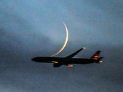 A plane is crossing over the moon crescent.