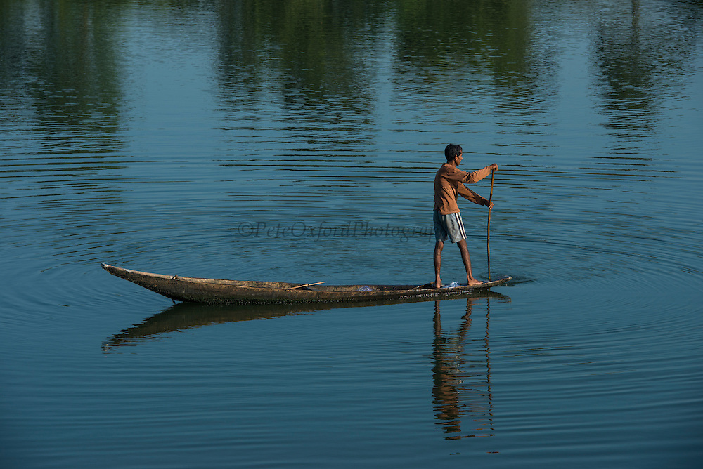 Fisherman in canoe<br /> Mising Tribe (Mishing or formally Miri Tribe)<br /> Majuli Island, Brahmaputra River<br /> Largest river island in India<br /> Assam,  ne India