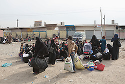 Licensed to London News Pictures. 10/11/2016. Mosul, Iraq. Women and children, escaping from areas within Mosul where fighting between Iraqi Security Forces and Islamic State militants are fighting, sit together as they wait to board a bus in the city's Gogjali District. The bus, provided by the Iraqi Army, will take them to the safety of a refugee camp in Iraqi-Kurdistan.<br /> <br /> The battle to retake Mosul, which fell June 2014, started on the 16th of October 2016 with Iraqi Security Forces eventually reaching the city on the 1st of November. Since then elements of the Iraq Army and Police have succeeded in pushing into the city and retaking several neighbourhoods allowing civilians living there to be evacuated - though many more remain trapped within Mosul. Photo credit: Matt Cetti-Roberts/LNP