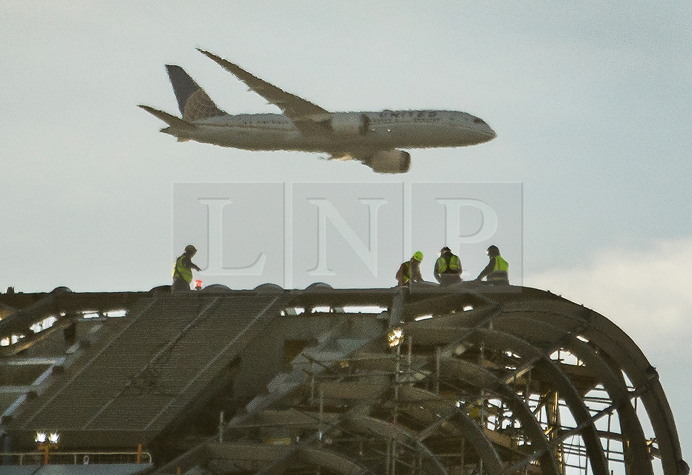 © Licensed to London News Pictures. 19/12/2017. London, UK. A passenger plane heading for Heathrow passes construction workers braving the cold as they work at the top of 'One Blackfriars' a sky scraper next to the River Thames - as parts of the UK are hit by fog and frost with travel disruption expected. The 52 storey apartment block began construction in 2013 and is 535 feet tall. Photo credit: Peter Macdiarmid/LNP