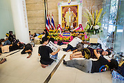 26 NOVEMBER 2013 - BANGKOK, THAILAND:  Thai anti-government protestors sit in front of a portrait of Bhumibol Adulyadej, the King of Thailand, in the lobby of the Ministry of Finance in Bangkok. Protestors opposed to the government of Thai Prime Minister Yingluck Shinawatra spread out through Bangkok this week. Protestors have taken over the Ministry of Finance, Ministry of Sports and Tourism, Ministry of the Interior and other smaller ministries. The protestors are demanding the Prime Minister resign, the Prime Minister said she will not step down. This is the worst political turmoil in Thailand since 2010 when 90 civilians were killed in an army crackdown against Red Shirt protestors. The Pheu Thai party, supported by the Red Shirts, won the 2011 election and now govern. The protestors demanding the Prime Minister step down are related to the Yellow Shirt protestors that closed airports in Thailand in 2008.    PHOTO BY JACK KURTZ