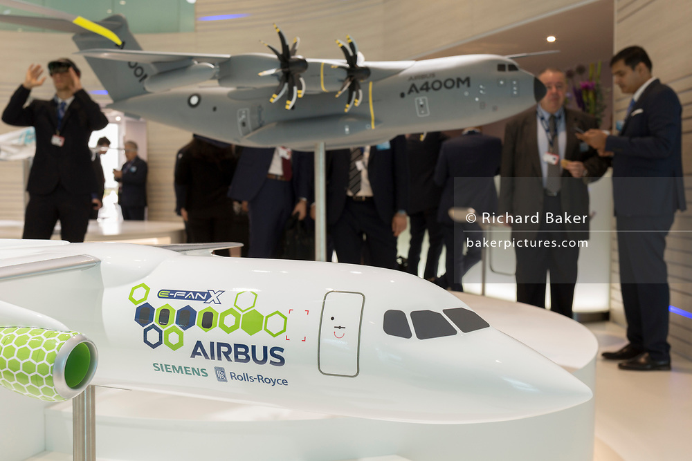 A scale model of the Airbus E-Fan X and A400M transporter aircraft and Airbus employees in the company's hospitality chalet at the Farnborough Airshow, on 18th July 2018, in Farnborough, England. The Airbus E-Fan is a prototype two-seater electric aircraft that was under development by Airbus.