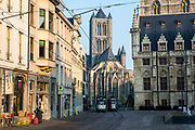 Street view of the historical centre of Ghent, Belgium.  Two electric trams travel along the tramway network past the beautiful architecture with St Nicholas Church in the background.
