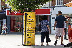 Wokingham, UK. 8th June, 2021. Local residents pass a Covid-19 public information display amid rising local concern regarding the spread of the Delta variant. Surge testing has been introduced in some local postcodes after a small number of cases of the Delta variant first identified in India were confirmed in the Wokingham area.