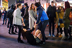 © Licensed to London News Pictures. 01/01/2017. London, UK. An intoxicated reveller is helped by friends as people celebrate the New Year in central London during the first hours of 2017 on January 1. Photo credit: Tolga Akmen/LNP