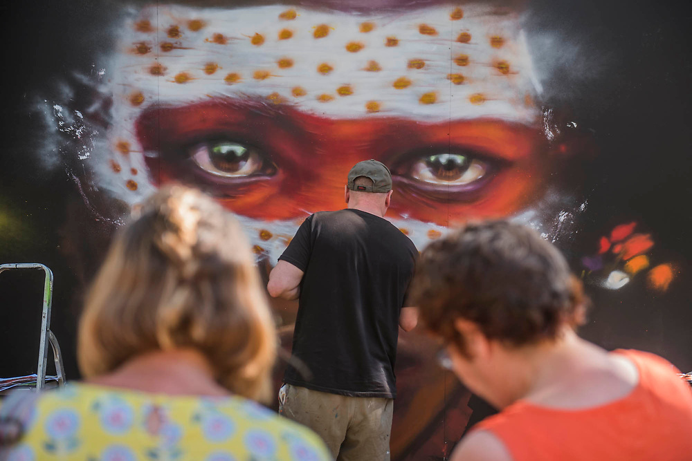 Dale Grimshaw works on his art in the woods - The 2018 Latitude Festival, Henham Park. Suffolk 14 July 2018