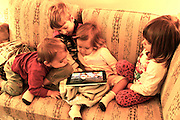 Four Children (cousins) watch video on iPad on home coach.