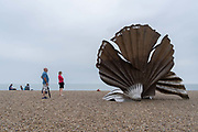 Families admire Scallop, a 4 metre high steel sculpture of two interlocking scallop shells on Aldeburgh beach dedicated to Benjamin Britten. Hamblings Scallop 2003 stands on the north end of Aldeburgh beach. It is a tribute to Benjamin Britten and is pierced with the words I hear those voices that will not be drowned from his opera, Peter Grimes, on 14th August 2020, in Aldeburgh, Norfolk, England.