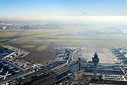 Nederland, Noord-Holland, Haarlemmermeer, 11-12-2013; luchthaven Schiphol met tegenlicht. Stationsgebouw en verkeertoren met vluchtleiding. Aan de gates geparkeerde vliegtuigen van onder andere KLM. Vliegtuig is zojuist opgestegen.<br /> Schiphol Airport with backlight. Terminal building and control tower surrounded by hotels and office buildings operated by Schiphol Real Estate (SRE). At the gates of parked aircraft, amongst others KLM. Plane has just taken off.<br /> luchtfoto (toeslag op standard tarieven);<br /> aerial photo (additional fee required);<br /> copyright foto/photo Siebe Swart