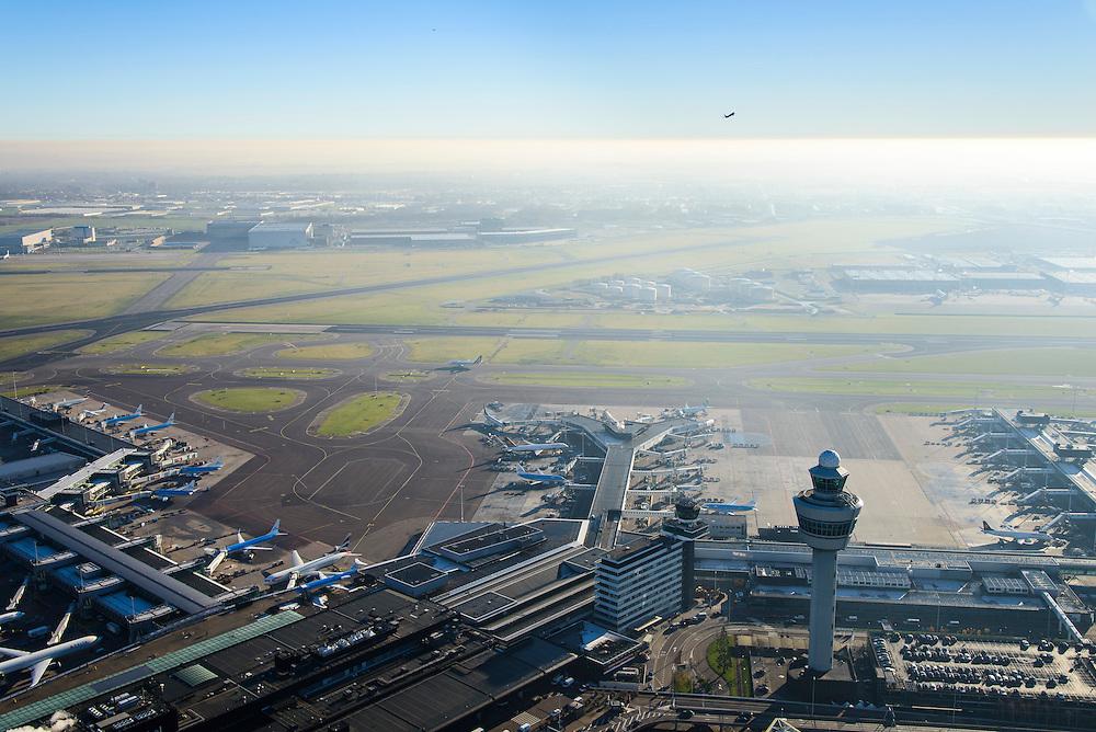 Nederland, Noord-Holland, Haarlemmermeer, 11-12-2013; luchthaven Schiphol met tegenlicht. Stationsgebouw en verkeertoren met vluchtleiding. Aan de gates geparkeerde vliegtuigen van onder andere KLM. Vliegtuig is zojuist opgestegen.<br /> Schiphol Airport with backlight. Terminal building and control tower surrounded by hotels and office buildings operated by Schiphol Real Estate (SRE). At the gates of parked aircraft, amongst others KLM. Plane has just taken off.<br /> luchtfoto (toeslag op standard tarieven);<br /> aerial photo (additional fee required);<br /> copyright foto/photo Siebe Swart