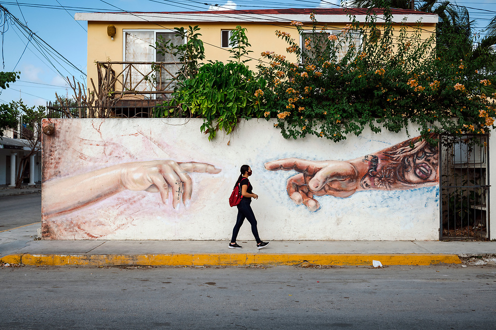 Tulum, Mexico - April 16, 2021: A woman walks past a street art mural in Tulum, Mexico