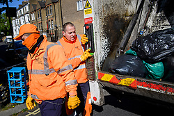 © Licensed to London News Pictures. 20/04/2020. London, UK.  Bin men Freddy, Mark under 'ganger' Ian Doherty work their route on Monday morning as usual in Hammersmith west London. Refuse collectors are obliged to continue working though the lockdown as councils face greater than normal waste disposal demands as the stay-at-home policy looks to continue into May. Local authorities have come under scrutiny over concerns about the lack of provision of basic protection against the coronavirus to key workers such as refuse collectors, transport operators and community care providers. Photo credit: Guilhem Baker/LNP
