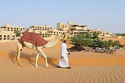 Arab man with camel at Qasr al Sarab Hotel by Anantara in Empty Quarter of Abu Dhabi United Arab Emirates