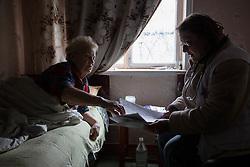 Doctor Svetlana Niekurasa consults with Svetlana Vorobyeva, 74, who suffers from hypertension and has become immobile in her home in Debaltsevo.
