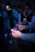 Students glimpse a bat held in the hands of a bat researcher during a bat survey at The Nature Conservacy's Dutch Henry Falls preserve in Central Washington.