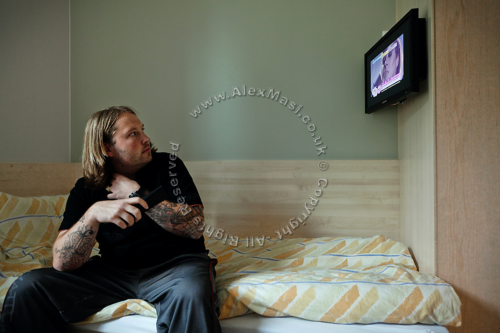 An inmate is watching television while sitting on his bed inside one of the private prison cells built with en-suite bathroom and various other amenities in the luxurious Halden Fengsel, (prison) near Oslo, Norway.