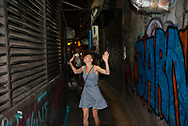 On a hot, muggy night, a young woman backpacking in Thailand cools off with the wind from a building's ventilation system. The location is an alley off of famous Khao San Road in Bangkok, Thailand (June 2017)