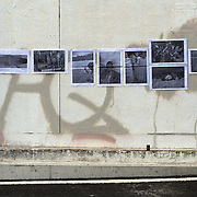 """""""Mira Mexico"""", newspaper exhibition installed on a wall in  Utsunomiya, Tochigi Prefecture, Japan July 6, 2013.<br /> (Credit Image: © Rachael Cerrotti )<br /> <br /> Curator<br /> Rachael Cerrotti (USA)<br /> <br /> Using photographs taken by Louie Palu relating to the Mexican drug war, this project challenges the reader to take apart this newspaper to see the full photographs and view the content. The goal is to force the reader to dismantle the vehicle used to deliver news and facts and thereby empower the reader to begin to think more critically. There are 16 photos in total, eight that do not relate to violence and eight that focus on violence or the drug business.. Each photograph is printed on a single sheet of newsprint, so if you take the newspaper apart each sheet of paper will have only one photograph on each side. Only eight pictures can be viewed at one time No photo can be entirely seen unless the reader opens and takes the newspaper apart. <br /> <br /> Once the newspaper comes apart it can be put back together in any order the reader wishes. The page spreads can also be hung as an exhibition. With violent images on one side and non-violent images on the other, the reader must become editor, curator or even censor, choosing how many violent photos are seen vs. how many non-violent photographs are seen. This forces the reader to face up to the fact that all delivery of news involves choices, of what to show and tell and what not to show and tell. It also forces the reader to face up to the system of institutions that serves as the gatekeepers in journalism and the visual arts. The questions are obvious. Is the editor censoring? Is the edit a true depiction of the news and the issue? Are violent images being used effectively to tell a story, or to sensationalize the story? The actual newspaper as an object forces the reader to engage in a a multidimensional exercise in journalism, art, and the politics of representation and message manipulation."""