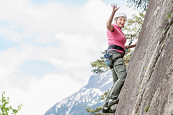 Female rock climber scaling a rock face and waving at Oberried climbing garden, Otztal, Tyrol, Austria
