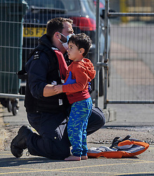 © Licensed to London News Pictures. 08/09/2021. Dover, UK. A Border Force officer helps a young migrant ashore as they arrive at Dover Harbour in Kent after crossing the English Channel. Fine weather is expected to see migrants attempt to cross the English Channel to the UK this week.  Photo credit: Stuart Brock/LNP