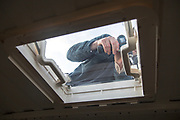 Cutting through roof of white metal camper van conversion to install ventilation window, UK